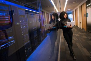 woman holding a laptop infront of a server room